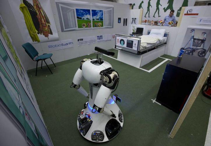 Amigo, un robot del tamaño de una persona, usa información colectada por otro robot para avanzar hacia una mesa a recoger un envase de leche y llevarlo a un paciente imaginario en una cama de hospital. (Agencias)