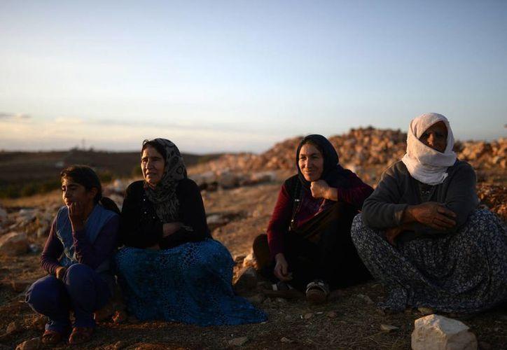 Refugiados sirios, en su mayoría curdos de Kobani, llegan a la frontera entre Turquía y Siria. (Foto AP)