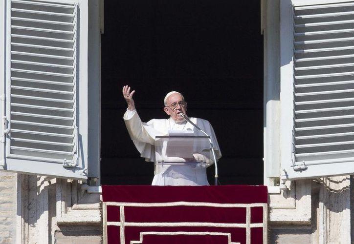 El Papa Francisco saluda durante la oración del Angelus desde la ventana de su despacho frente a la Plaza de San Pedro, el domingo 15 de enero de 2017 en el Vaticano. (AP Foto/Andrew Medichini)