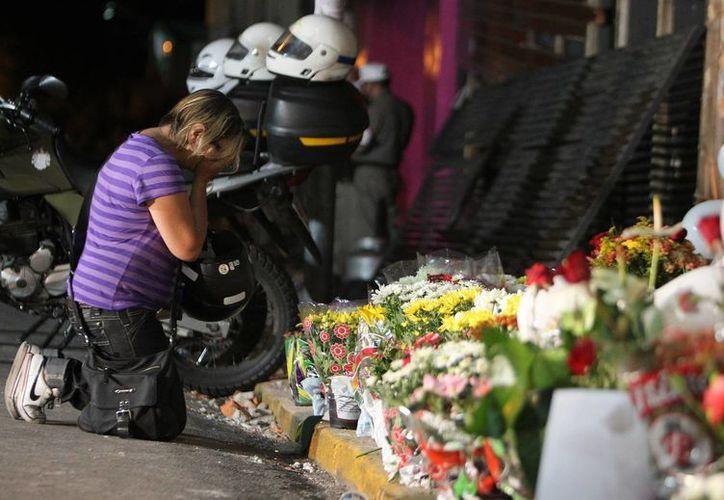 Una familiar de una de las víctimas del incendio deposita una ofrenda en el lugar. (Agencias)