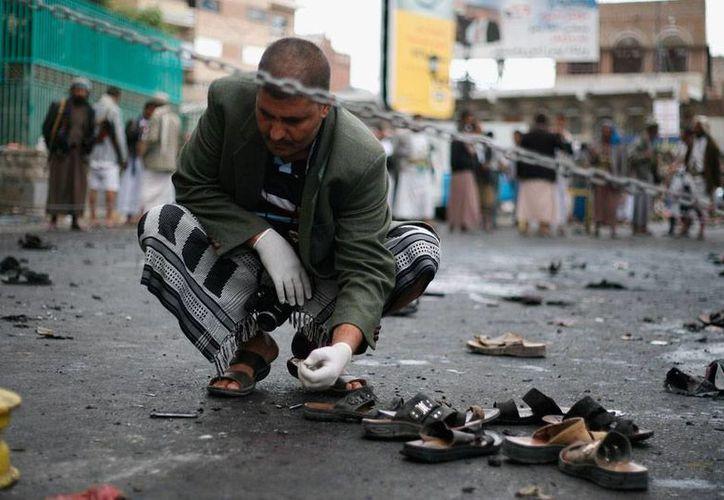 Un oficial revisa la zona en donde este jueves hubo un atentado, en Sana, Yemen. El saldo preliminar es de 40 muertos. (AP)