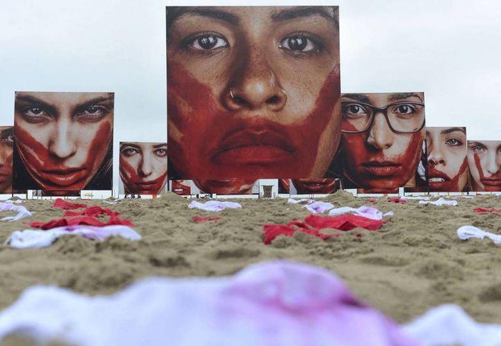 La violencia sexual es invisible en las zonas más pobres de Río de Janeiro. En la foto, exposición en la playa de Copacabana contra la violencia de género. (elpais.com)