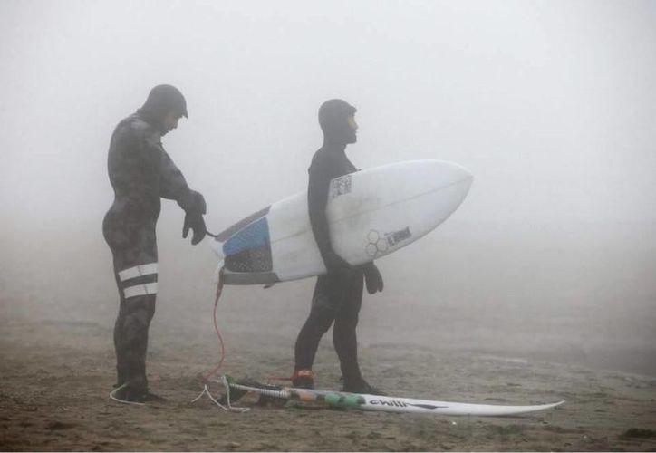 New York registró una Navidad con temperaturas altas históricas. Esto, combinado con el buen oleaje permitieron la inhabitual llegada de decenas de surfistas a la playa de Rockaway Beach, desde altas horas en este 25 de diciembre. (AP)