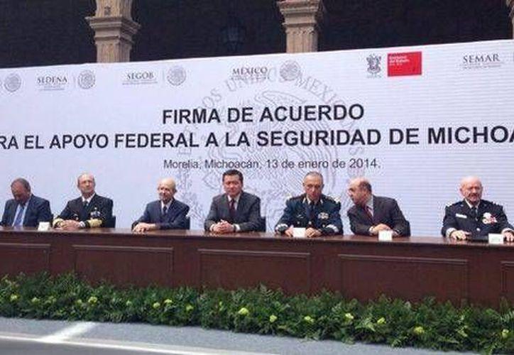 El secretario de Gobernación, Miguel Osorio Chong, y el gobernador de Michoacán, Fausto Vallejo, durante la firma del acuerdo para el Apoyo Federal. (@gobmichoacan)
