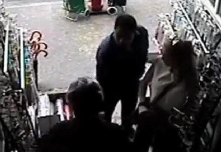 El asaltante (de frente) sujeta a Edith González mientras le exige a ella ya su esposo (de espaldas) que le entreguen sus relojes. (Captura de pantalla de YouTube)