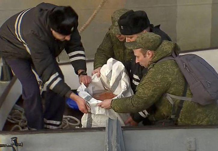 La televisora estatal mostró imágenes de rescatistas en una balsa hinchable portando un contenedor con un objeto naranja brillante cubierto de agua. (Imagen del canal de televisión Rossiya One vía AP)