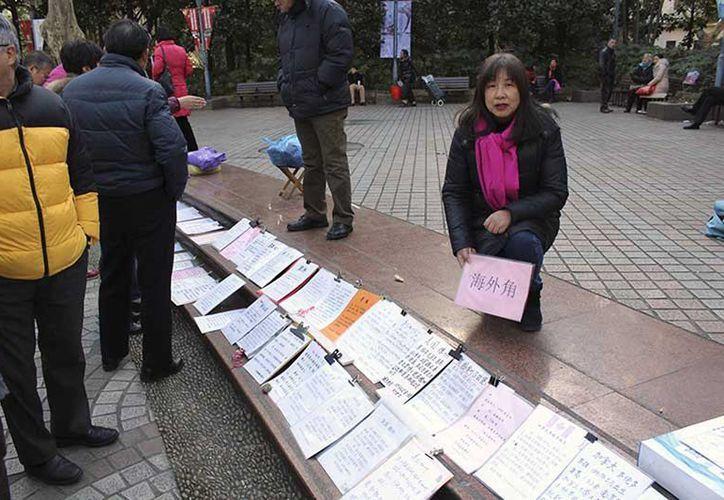 Una mujer coloca el anuncio de su hijo soltero, en el Parque del Pueblo de Shangai, donde se instala un mercado de matrimonios. China es un país en el que los padres se resisten a que sus hijos elijan la soltería como forma de vida. (EFE vía  Excélsior)