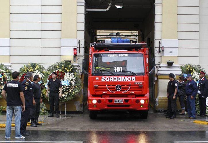 Un carro de bomberos sale de la sede de la Policía Federa, donde se realiza el velorio de los seis bomberos de muertos en un incendio, en Buenos Aires, Argentina. (EFE)
