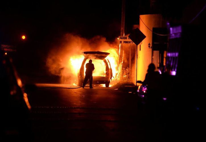 Empleados de un centro de servicio auxiliaron a los ocupantes de un automóvil que se incendió muy cerca de la avenida Canek. (Cuauhtémoc Moreno)