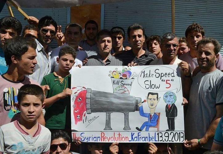 Manifestantes anti-régimen sirio con un dibujo del presidente de Siria. (Agencias)