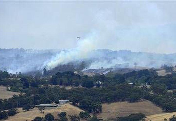 Un avión vuela sobre humo proveniente de incendios cerca de Adelaida, Australia,el sábado 3 de enero de 2015. (Foto: AP/OAAP/David Mariuz)