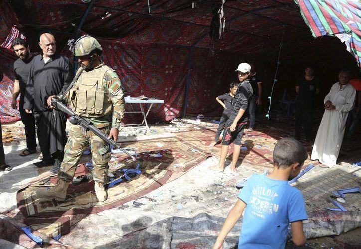 Pobladores y fuerzas de seguridad iraquíes se reúnen en el sitio de un ataque suicida con bomba en el norte del distrito Shaab de la ciudad de Bagdad, Irak. (AP/Karim Kadim)