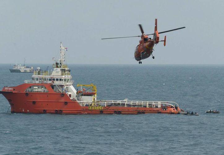 Un helicóptero sobrevuela el lugar en el que los buzos indonesios trabajan en las labores de búsqueda del accidente del avión de AirAsia. (Archivo/EFE)