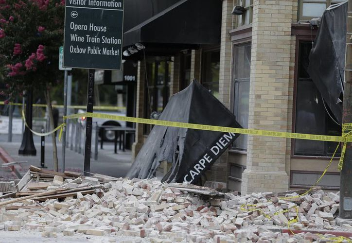 Ladrillos y anuncios tirados se observan en una calle comercial de Napa, California, que evidencias los daños causados por el fuerte temblor registrado la madrugada del domingo. (Foto: AP/ Eric Risberg)