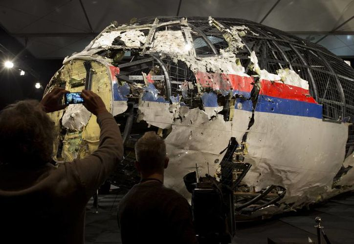 Periodistas toman imágenes de la parte de la sección reconstruida delantera del fuselaje del avión MH17 de Malaysia Airlines. (Agencias)
