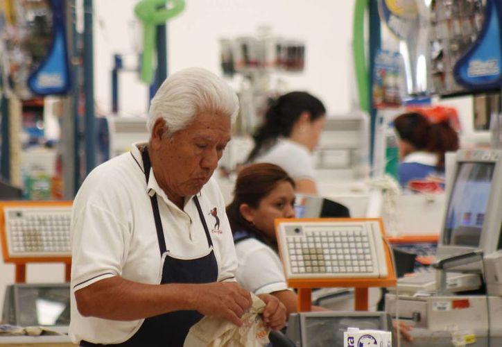 La tasa de la gente de 15 años y más, en edad de trabajar, se ubicó en 59.2 por ciento. Imagen de un anciano que labora como 'cerillo' en un supermercado, utilizada solo con fines ilustrativos. (Archivo/SIPSE)