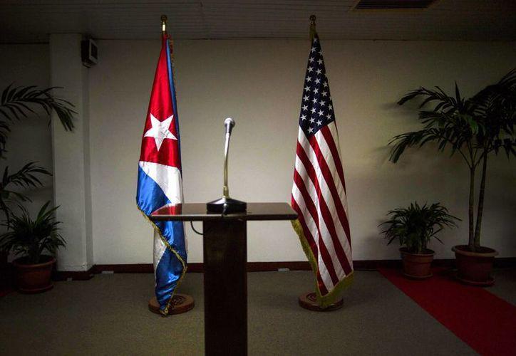 Imagen de una bandera cubana y estadounidense de pie ante el inicio de una conferencia de prensa en el marco de las conversaciones entre las dos naciones en La Habana, Cuba. (Agencias)