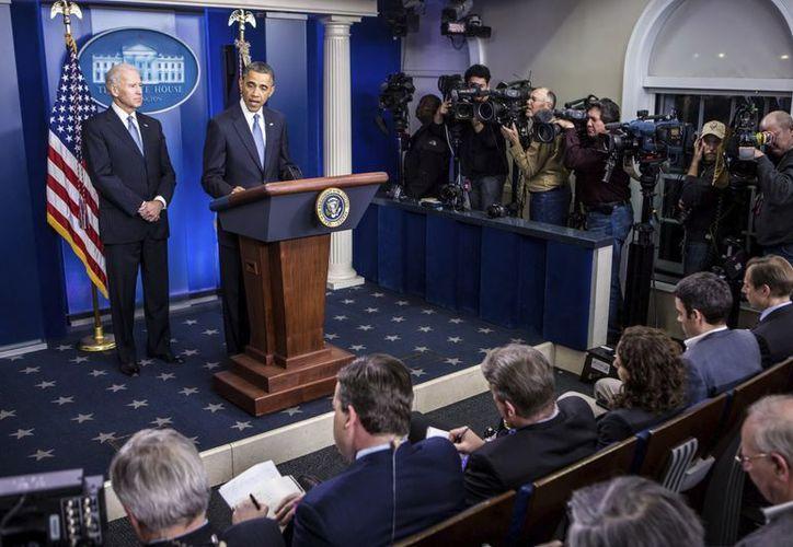 El vicepresidente Joseph Biden escucha al presidente Obama durante su declaración a los medios en la Casa Blanca, luego de que se evitara el llamado 'precipicio fiscal'. (EFE)