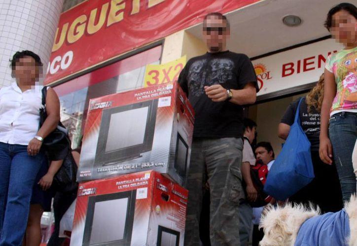 Las ofertas de El Buen Fin atraen a yucatecos. Imagen de un hombre con dos televisores saliendo de una tienda departamental. (Milenio Novedades)