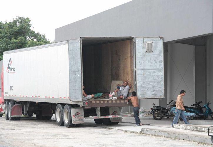 Arriba camión con máquinas de la empresa transportista Gutiérrez. (Julián Miranda/SIPSE)