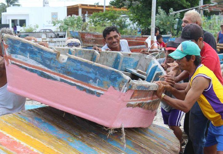 Imagen de un grupo de pescadores de Progreso mientras resguardan una lancha, ante la ola de robos que existe en la costa de Yucatán. (Gerardo Keb/Milenio Novedades)