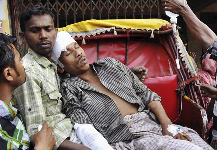 Un manifestante lesionado en el marco de las protestas anti comicios es atendido en  Shatkaniya, afuera de Chittagong, en Bangladesh. (Agencias)