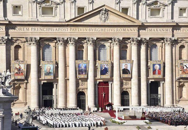 Los retratos de los siete nuevos santos, sobre la fachada de la basílica de San Pedro en el Vaticano. (EFE)