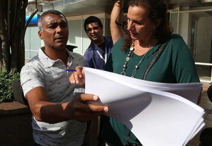 El exfutbolista y diputado federal Romario (i) entrega un documento con 50 mil firmas pidiendo la salida del presidente de la CBF, José Marin. (EFE)