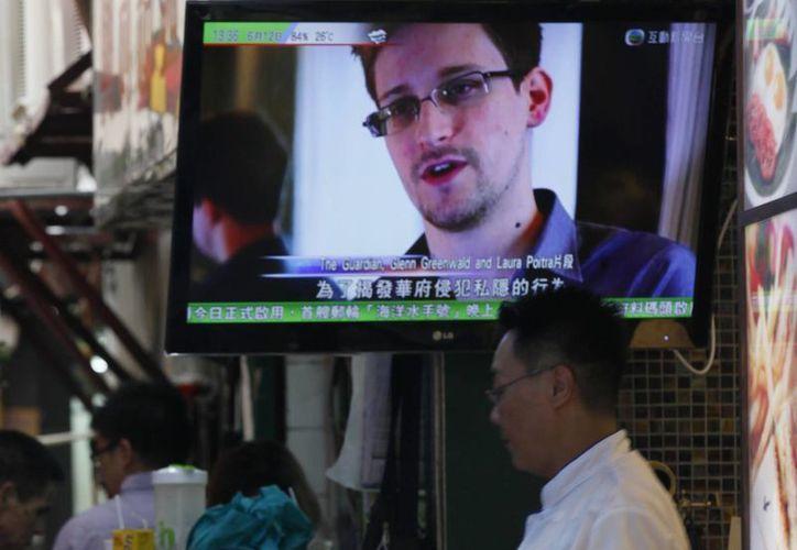 Una televisión muestra al exempleado de la CIA que filtró documentos secretos sobre los programas de espionaje interior en EU, en un restaurante de Hong Kong. (Agencias)