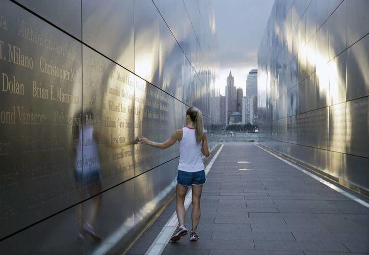 """Una corredora se detiene a mirar los nombres de las víctimas de los ataques del 11-S en el monumento """"Empty Sky"""". (Agencias)"""