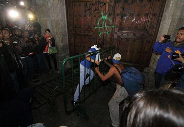 Algunos jóvenes tomaron una de las vallas metálicas que resguardaba el edificio para golpear la puerta principal del  Palacio Nacional e intentar ingresar. (Omar Franco/Milenio)