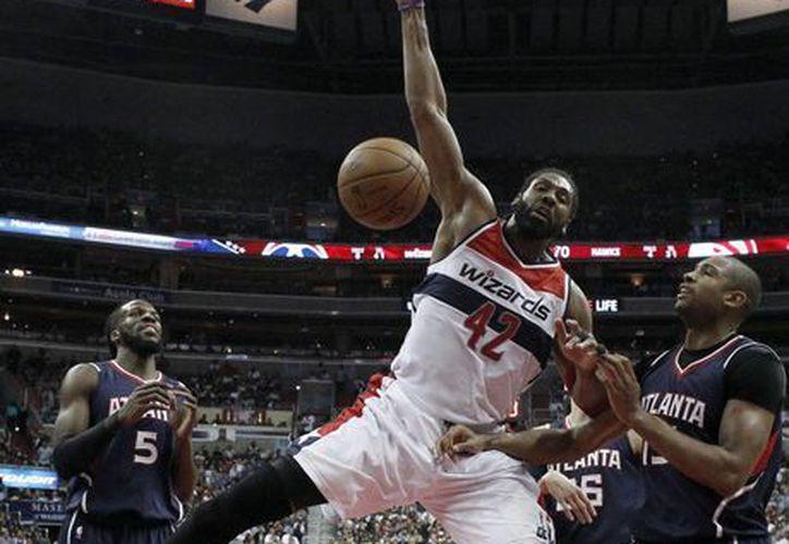 Nene (42), brasileño de Wizards, hunde la pelota entre DeMarre Carroll (5) y  Al Horford, de Hawks, en partido ganado por Atlanta para empatar a 2 la serie de postemporada de la NBA. (Foto: AP)