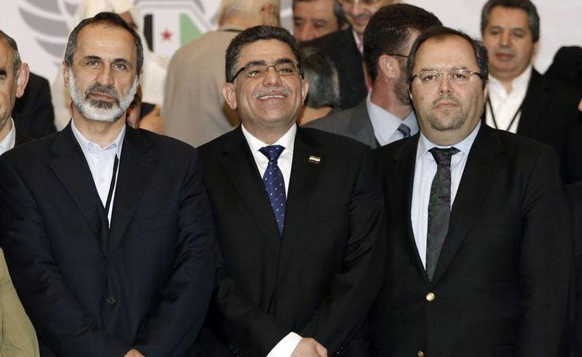 El primer primer ministro sirio Gasan Hito (c), con Muaz al Jatib (i) y el secretario general de la coalición Mustafa Sabbagh. (EFE/Archivo)