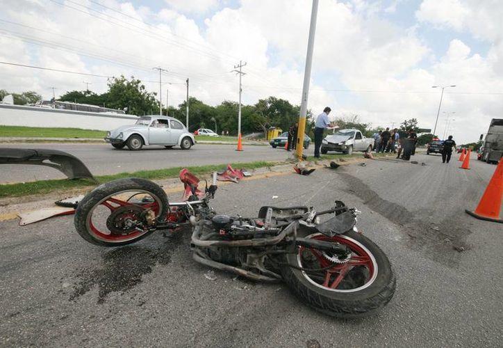 La motocicleta quedó desbaratada tras ser impactada por una camioneta en la carretera Mérida-Umán. (Milenio Novedades)