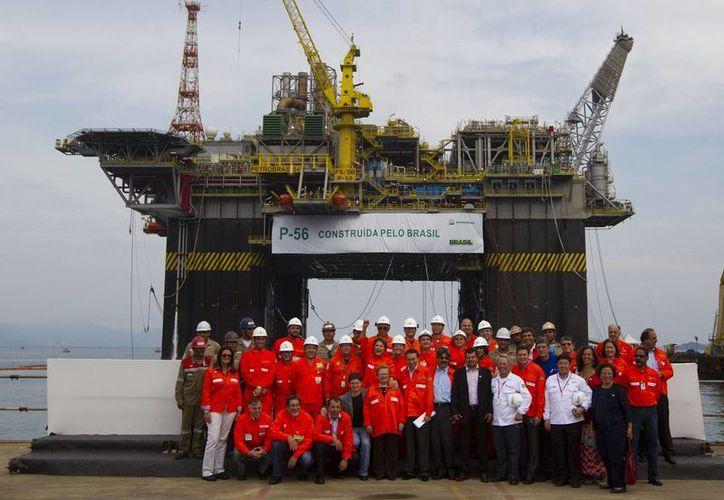 En imagen del 3 de junio de 2011, la presidenta Dilma Rousseff posa con trabajadores en la plataforma petroleta P-56 de Petrobras en Angra dos Reis, Brasil. (Foto AP/Felipe Dana, archivo)