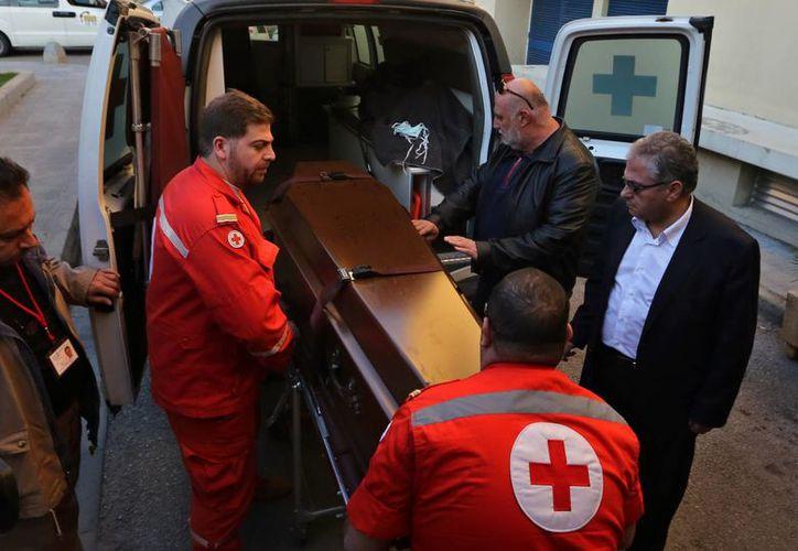 Miembros de la Cruz Roja portan el féretro con los restos del médico británico Abbas Khan, de 32 años, a su llegada a Beirut. (Agencias)