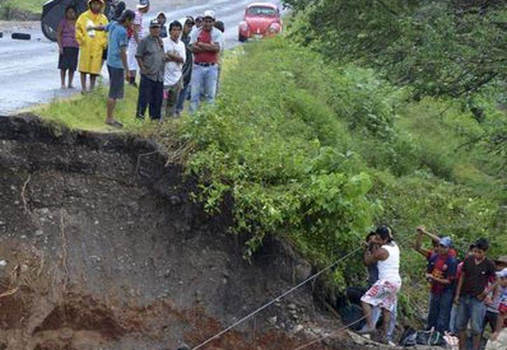 Mexicanos se las arreglan para cruzar un río donde un puente se colapsó en Petaquillas, Guerrero. (Agencias)