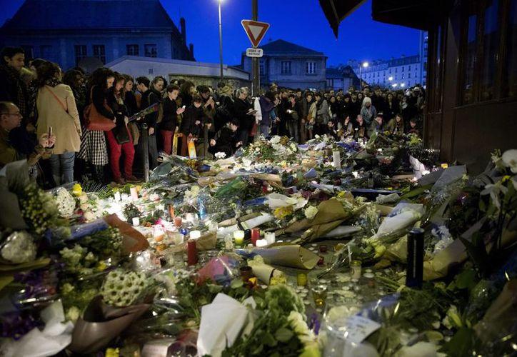 Personas depositan flores y velas en homenaje a las víctimas de los atentados terroristas en la noche del viernes en París, Francia. (EFE)