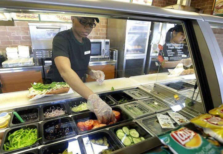 Trabajadores hacen sándwiches en una franquicia de Subway en Seattle. La empresa prometió garantizar que sus sándwiches midan 30 cm para resolver una demanda colectiva. (Agencias)