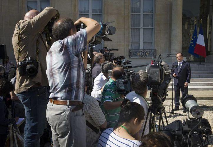 El presidente francés, François Hollande (d), se dirige a los medios de comunicación momentos después de un consejo de ministros extraordinario por el caso del avión Air Algérie, celebrado en el Palacio del Elíseo. (EFE)