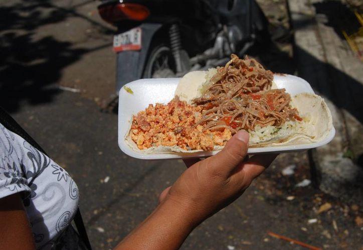 La gente consume comida en la calle por sus empleos y la falta de tiempo. (Tomás Álvarez/SIPSE)
