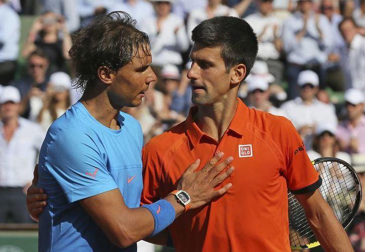 El tenista serbio Novak Djokovic (der.), número uno del mundo, venció en tres sets a Rafa Nadal, máximo ganador en la historia de Roland Garros, por marcador de 7-5, 6-3, 6-1 en partido de cuartos de final. (AP)