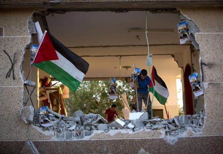 Palestinos instalan banderas en la casa de  Bashar Masalha, demolida por el Ejército israelí en la villa de Hajja, cerca de la ciudad de Nablus, el martes 21 de junio de 2016. (Foto: AP)