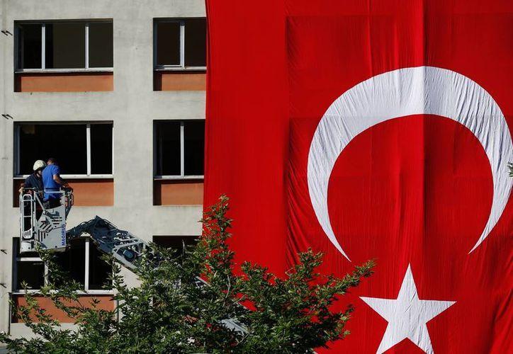 Trabajadores cubren con una bandera turca la fachada de un edificio dañado el martes en una explosión en Estambul, Turquía. (Agencias)