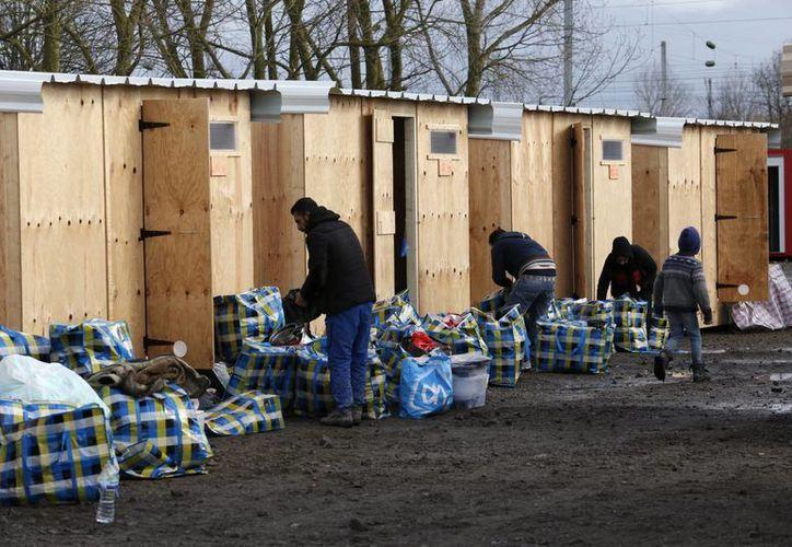 Varios refugiados se trasladan a sus cabañas en un campamento habilitado por la organización Médicos sin Fronteras (MSF) en Grand Synthe, cerca de Calais (Francia), el pasado mes de marzo. (EFE/Archivo)