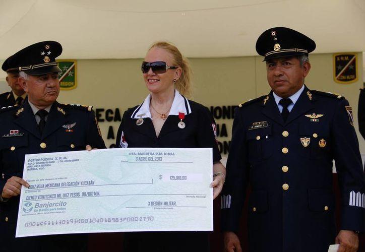 La delegada de la Cruz Roja, Michelle Byrne (i), al recibir el cheque en compañía del   general Vélez Fernández. (SIPSE)