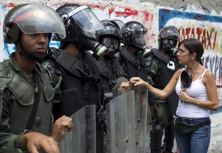 Una mujer habla con miembros de la Guardia Nacional Bolivariana, durante una protesta con ollas vacías contra el Gobierno del presidente venezolano, Nicolás Maduro. (EFE)