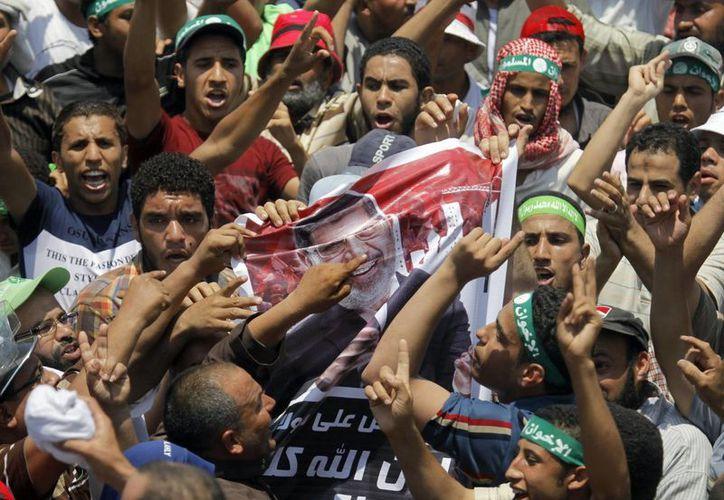 Ciudadanos apoyan al presidente Morsi afuera del palacio presidencial en El Cairo. (Agencias)
