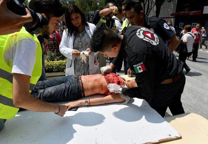 Rescatistas de Bomberos y policías trabajan en el rescate y atención de lesionados. (Foto: CNN)