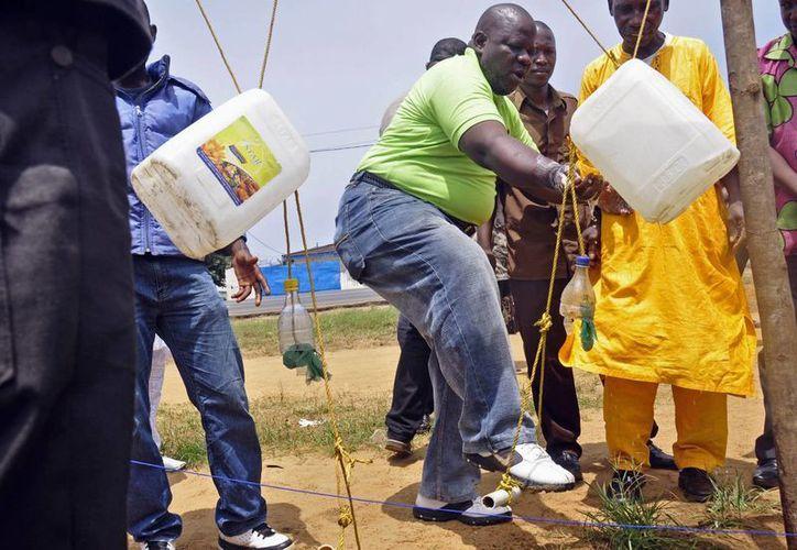 Personas se lavan las manos con desinfectante como una medida preventiva contra el virus del ébola, en la ciudad de Monrovia, Liberia. (Agencias)
